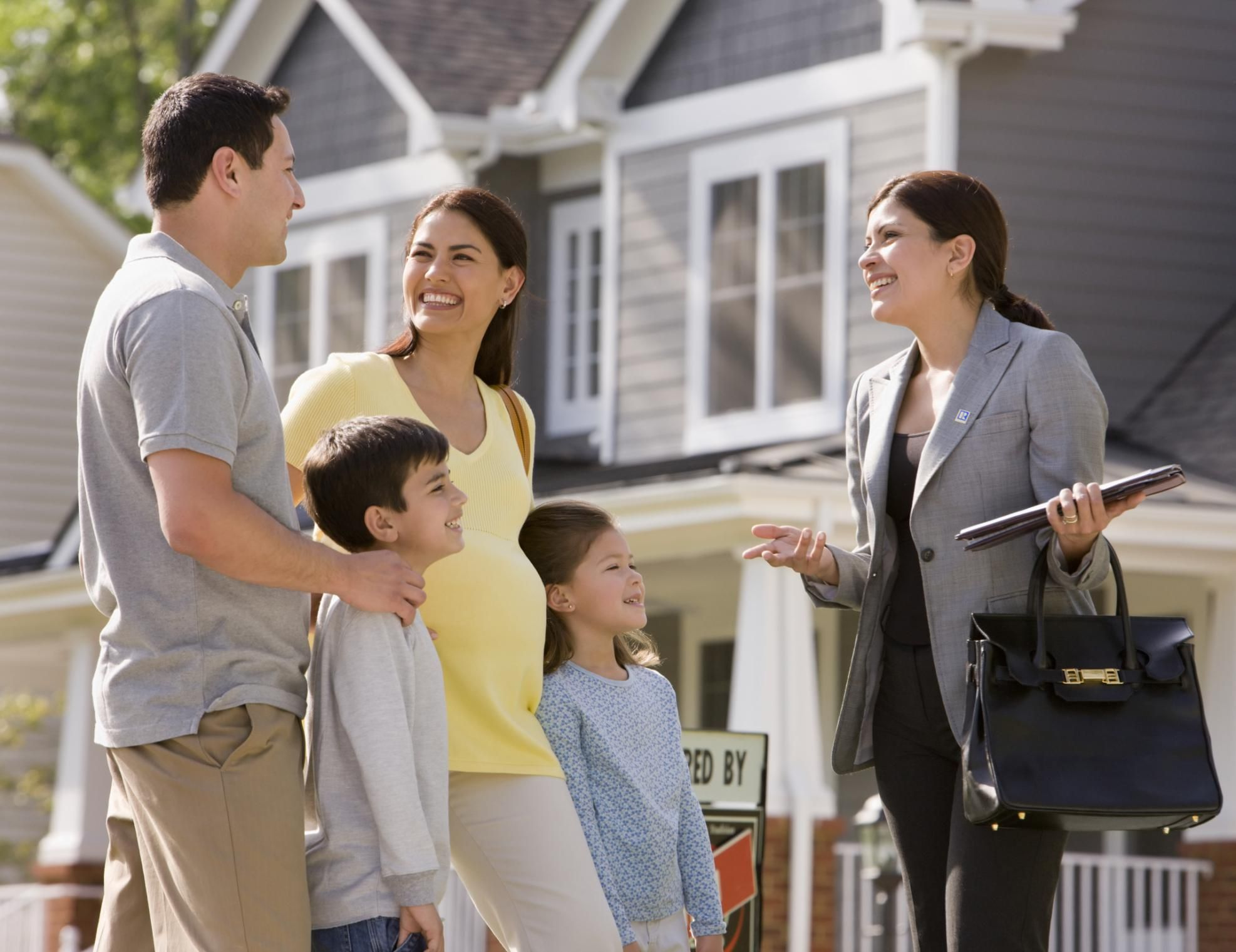 A family and property agent smiling in front of home